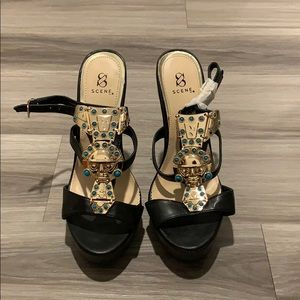 Black heels with turquoise and gold details.